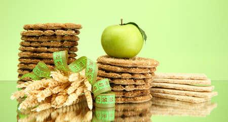 tasty crispbread, apple, measuring tape and ears, on green background Stock Photo - 16087000