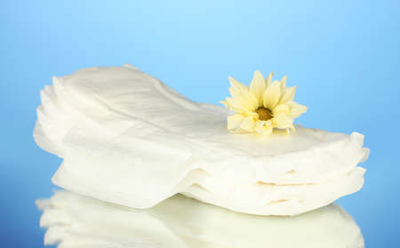 Panty liners and yellow flower on blue background close-up photo