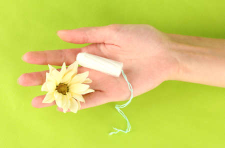 womans hand holding a clean cotton tampon on green background close-up photo