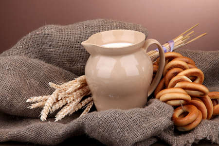 jar of milk, tasty bagels and spikelets on wooden table, on brown background photo