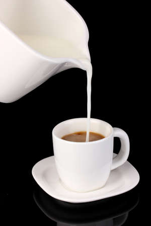poured: Delicate cream poured into cup of coffee isolated on black