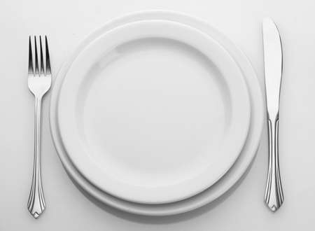 setting table: White empty plate with fork and knife isolated on white