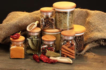jars and spoons with spices on wooden table on black background photo