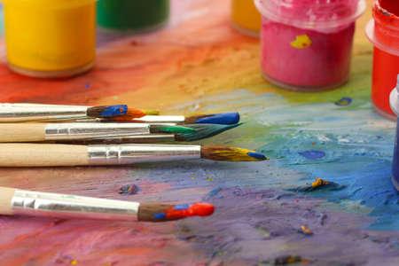 pintora: paleta de madera del arte con la pintura y los pinceles, primer plano