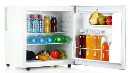 mini fridge full of bottles of juice, soda and fruit isolated on white photo