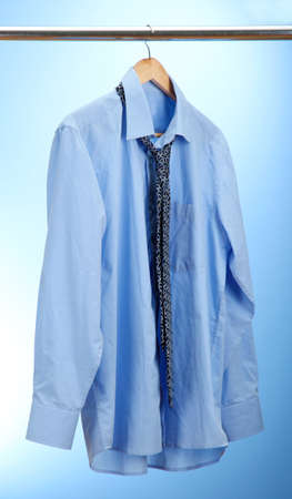 shirt with tie on wooden hanger on blue background photo