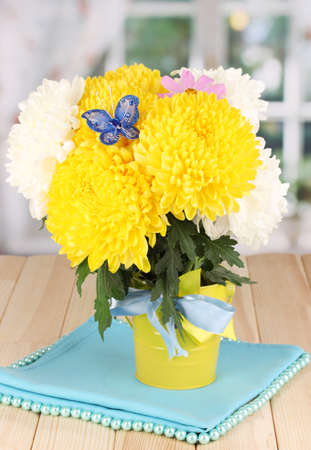 Beautiful chrysanthemum in pail on wooden table on window background photo
