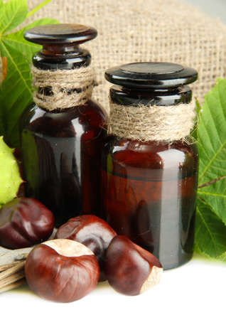 medicine bottles with chestnuts and leaves, on burlap background photo
