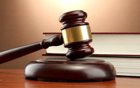 martillo juez: Mazo de madera y libros sobre la mesa de madera, sobre fondo marr�n
