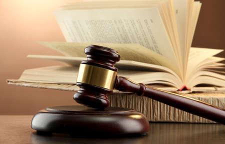 legal document: Mazo de madera y libros sobre la mesa de madera, sobre fondo marr�n
