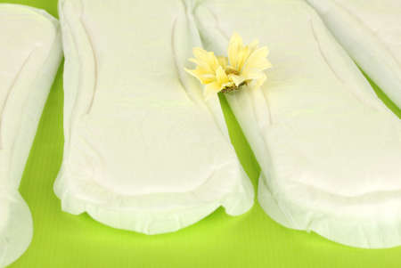 Panty liners and yellow flower on green background close-up