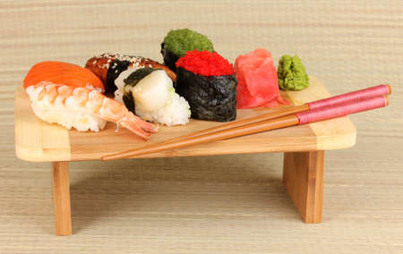 delicious sushi served on wooden board on bamboo mat photo