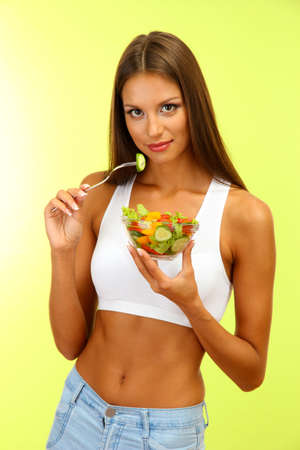 beautiful young woman with  salad, on green background photo