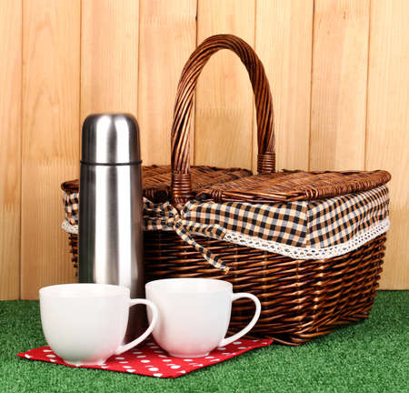 metal thermos with cups and basket on grass on wooden background photo