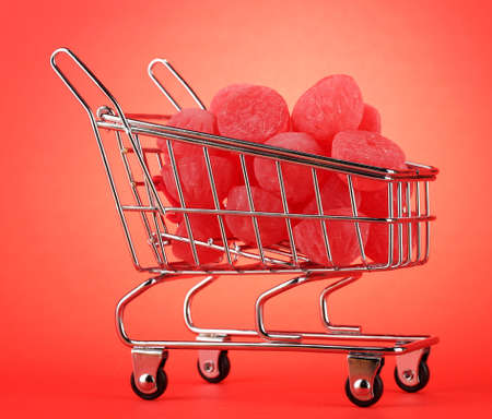 shopping trolley with jelly candies, on red background Stock Photo - 16107535