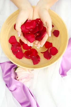 handcare: woman hands with wooden bowl of water with petals Stock Photo