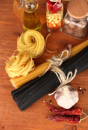 Pasta spaghetti, vegetables and spices on wooden table on wooden background photo