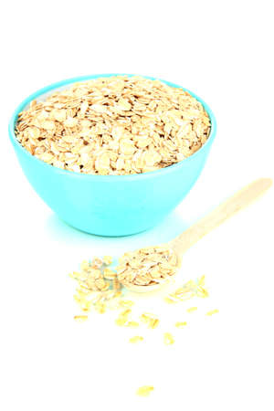 Blue bowl full of oat flakes with wooden spoon isolated on white photo
