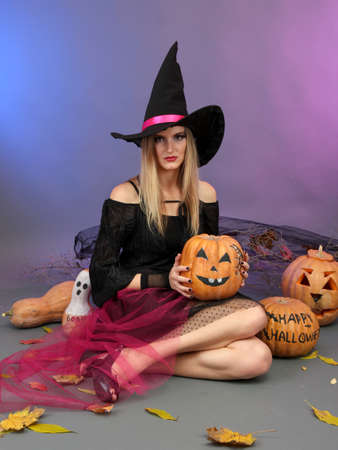Halloween witch holding pumpkin on color background photo