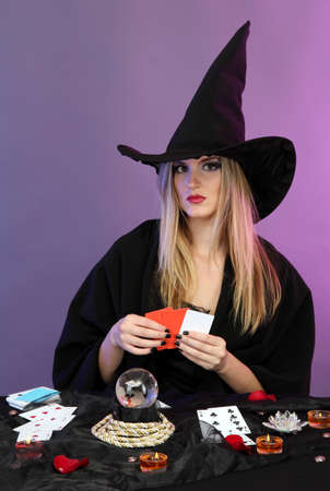 Witch - fortuneteller on color background photo