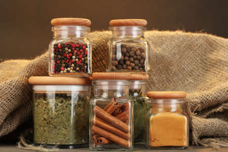 jars with spices on wooden table on brown background photo