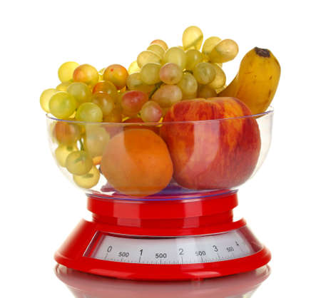 Ripe fruit in kitchen scales isolated on white photo