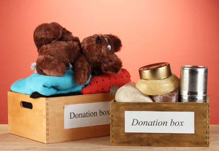 Donation boxes with clothing and food on red background close-up Stock Photo - 16132391