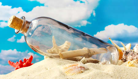 castaway: Glass bottle with note inside on sand, on blue sky background Stock Photo