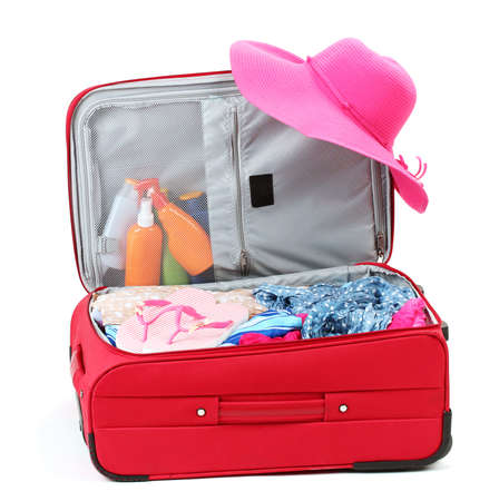 haversack: Suitcase with summer clothes, a hat and suntan isolated on white