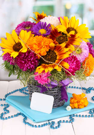 ronantic: Beautiful bouquet of bright flowers with paper note on wooden table on window background