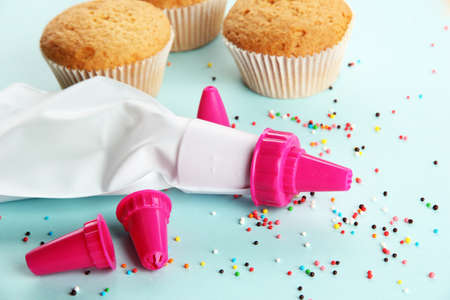 confectionery bag with replaceable nozzles and cake, on blue background photo