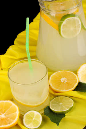 Citrus lemonade in glass and pitcher of citrus around on yellow fabric on wooden table close-up Stock Photo - 16132348