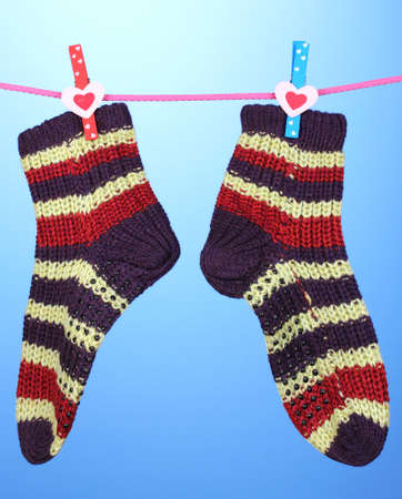 Pair of knit striped socks hanging to dry over blue background Stock Photo - 16132365