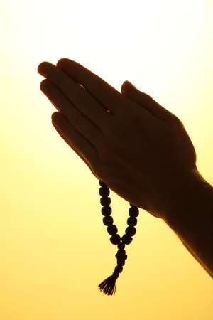 male hands with rosary, on yellow background Stock Photo - 16131828