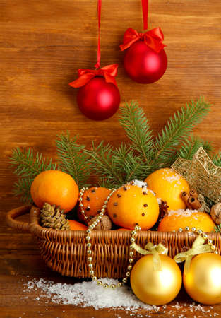 mandarin: christmas composition in basket with oranges and fir tree, on wooden background Stock Photo