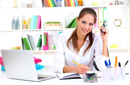 Young pretty business woman with notebook in office Stock Photo - 16346067