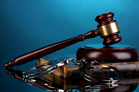 Gavel, handcuffs and book on law on blue background photo