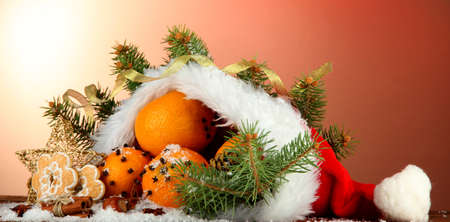 christmas composition with oranges and fir tree in Santa Claus hat photo