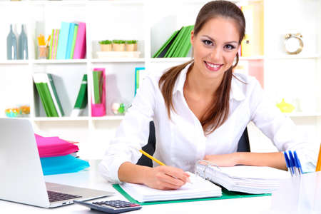 Young pretty business woman with notebook in office Stock Photo - 16346044