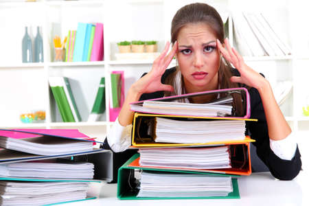 overload: tired business woman with documents in her workplace