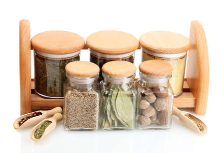 jars and wooden spoons on shelf with spices isolated on white photo