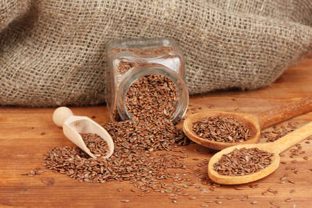 Flax seeds in wooden spoons on wooden background close-up photo
