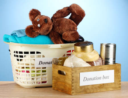 Donation boxes with clothing and food on blue background close-up photo
