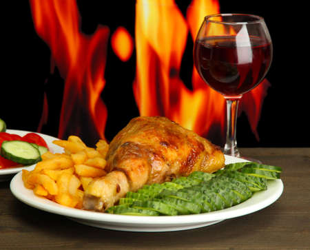 oven chicken: Roast chicken with french fries and cucumbers, glass of wine on wooden table  on fire background Stock Photo