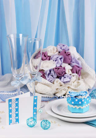 a frill: Serving fabulous wedding table in blue color on blue and white fabric background