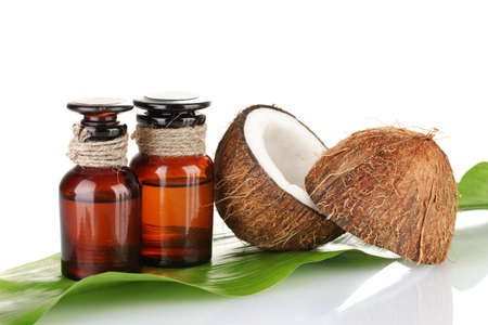 coconut oil in bottles with coconuts on white background photo