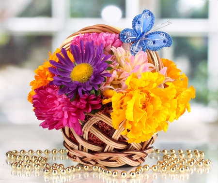 Beautiful bouquet of bright flowers in small basket with paper note on white table on window background photo