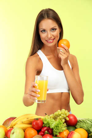 beautiful young woman with fruits and vegetables and glass of juice, on green background Stock Photo - 16546785