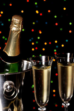 Celebratory champagne with stemware on Christmas lights background photo