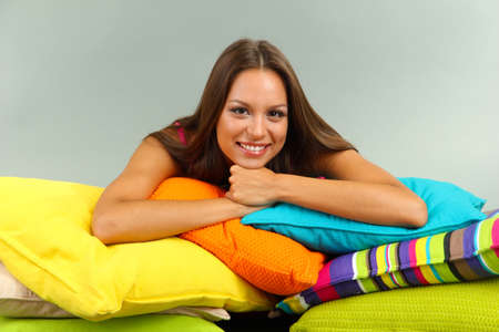 beautiful young girl with pillows on grey background photo